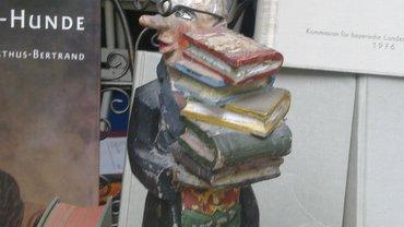 Holzfigur mit Bücherstapel
