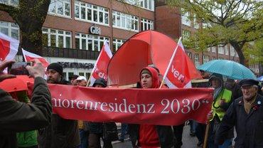 """Demo-Teilnehemer*innen tragen eine Strandmuschel mit dem Untertitel """"Seniorenresidenz 2030"""""""