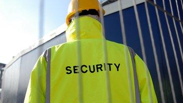 Mann in Securitiy-Weste von hinten