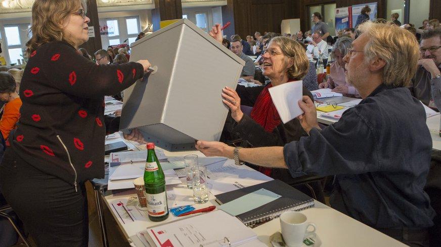 Delegierte stecken Stimmzettel in eine Urne