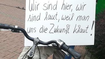"""Schild: """"Wir sind hier, wir sind lau, weil man uns die Zukunft klaut"""""""
