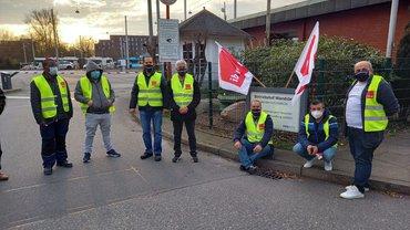 Eine Gruppe streikender Kolleg*innen bei TEREG, steht mit Abstand und Maske vor dem Tor zu einem Betriebshof.