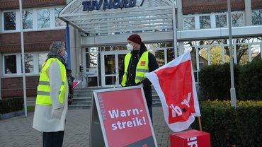 stay@home-Streik: Nur ein kleiner Streikposten. Zwei Menschen in ver.di-Weste unterhalten sich mit Abstand und Maske.