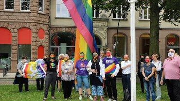 Kolleg*innen vor der Regenbogenflagge am DGB-Haus