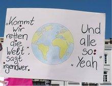"""Schild mit der Aufschrift """"Lasst uns die Welt retten"""""""
